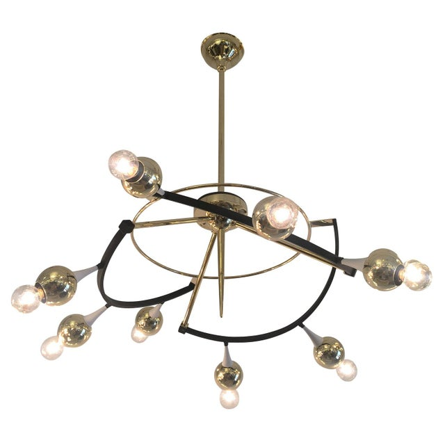 Exceptional orbital chandelier by Stilnovo featuring nine round brass shades. The elliptical frame is brass as well as...