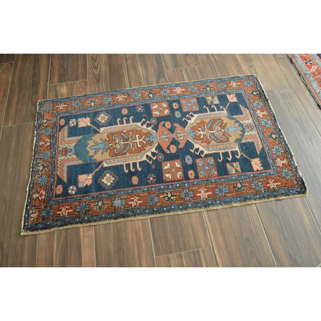 Antique Heriz rug featuring an archaic double medallion pattern. Palette includes: navy, brick, light blues, pink, salmon,...
