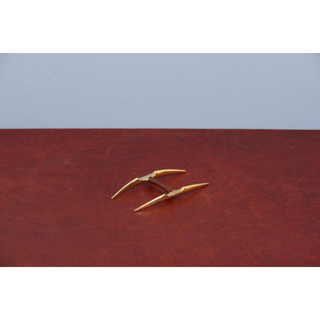 Exceptional pen or paintbrush rest by Carl Auböck in brass and leather.
