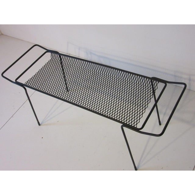 A black iron framed catch all or magazine rack with handles to each side and perforated basket.