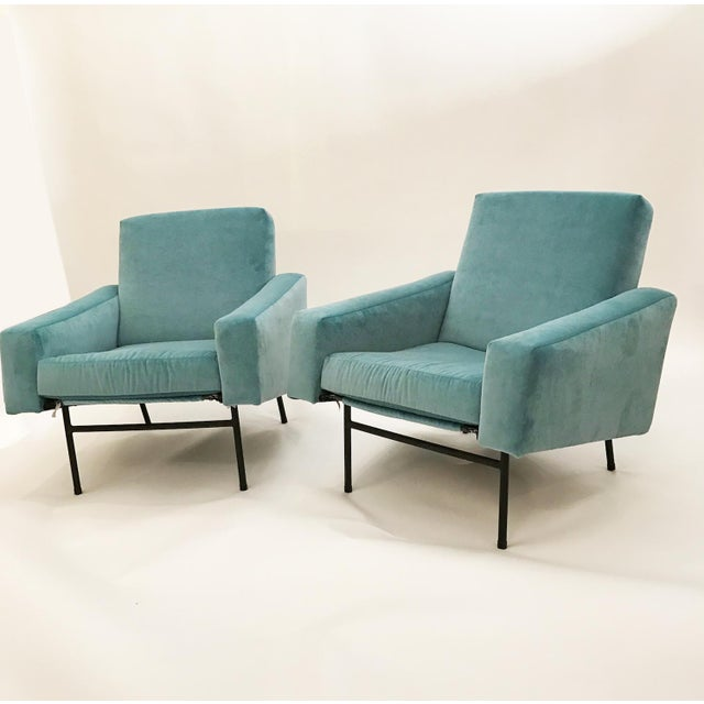 Pierre Guariche Pair of club chairs each featuring tight seats and backs with angled tight armrests which are supported by...