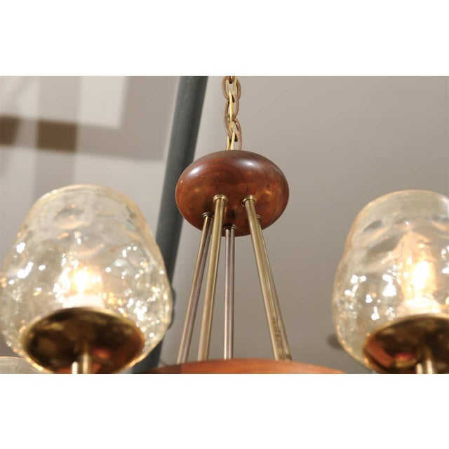 Mid-century five light teak and brass chandelier with champagne colored glass globes and an iridescent pearl finish. Circa...