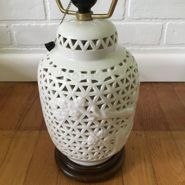 "Beautiful pierced white porcelain accent lamp on wooden base with lit interior. Measures 13.5"" to top of socker and 18.5""..."