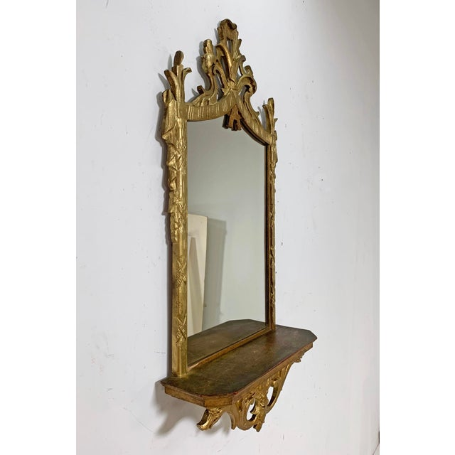 Italian carved giltwood mirror with under shelf, circa 1950s. Elaborate top garland carvings with side pedestals of Roman...