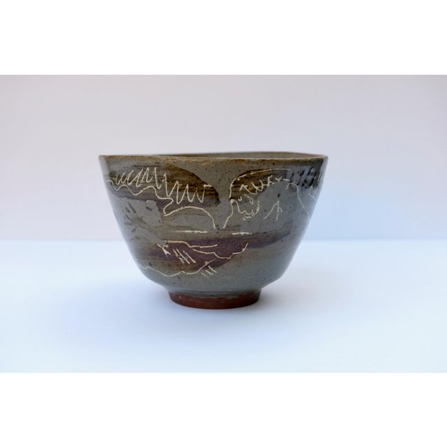 Incredible footed glazed bowl with figural design of two angels. There is a vine connecting the two figures. The brown...