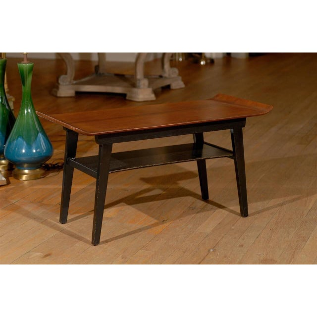 A Mid-Century coffee table or side table with a wooden top with an upturned ends on an ebonized base with a shelf.