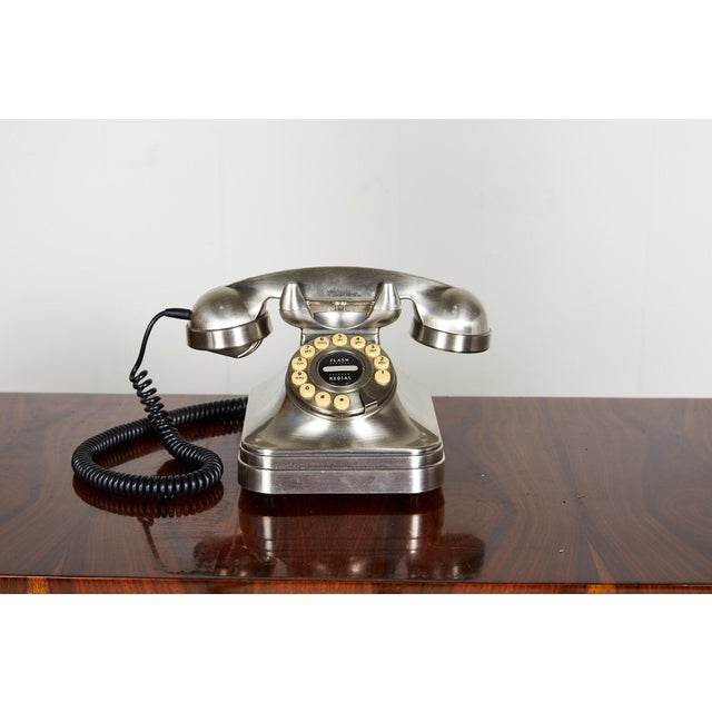Late 20th Century retro style phone in a brushed nickel finish with a push button rotary.