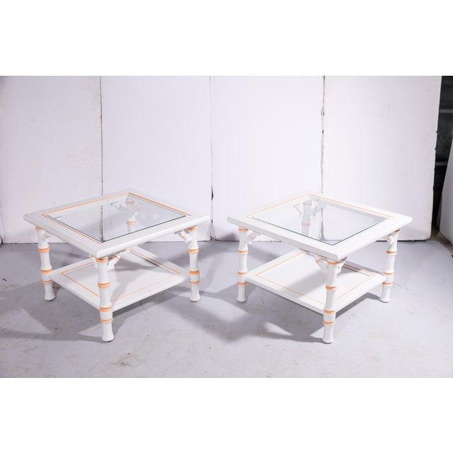 Pair of vintage white faux-bamboo side tables with coral-hued accents, removable inset glass tops, and white painted...