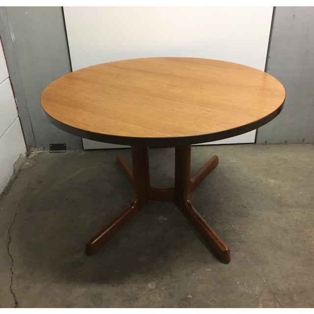 Teak round coffee table by Dyrlund with those awesome skinny clown foot x-base legs so emblematic of Dyrlund. Heavy table....