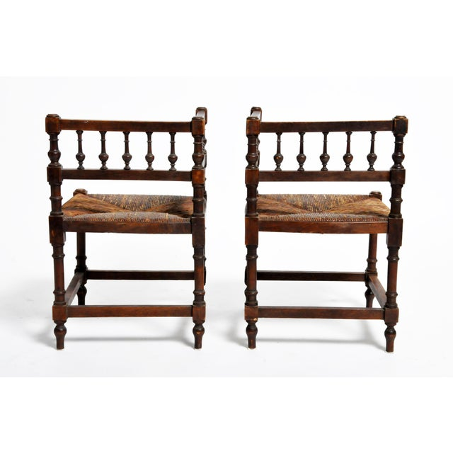 This pair of wooden corner chairs is from France and was made circa 1900. Strong and sturdy, the chairs feature...