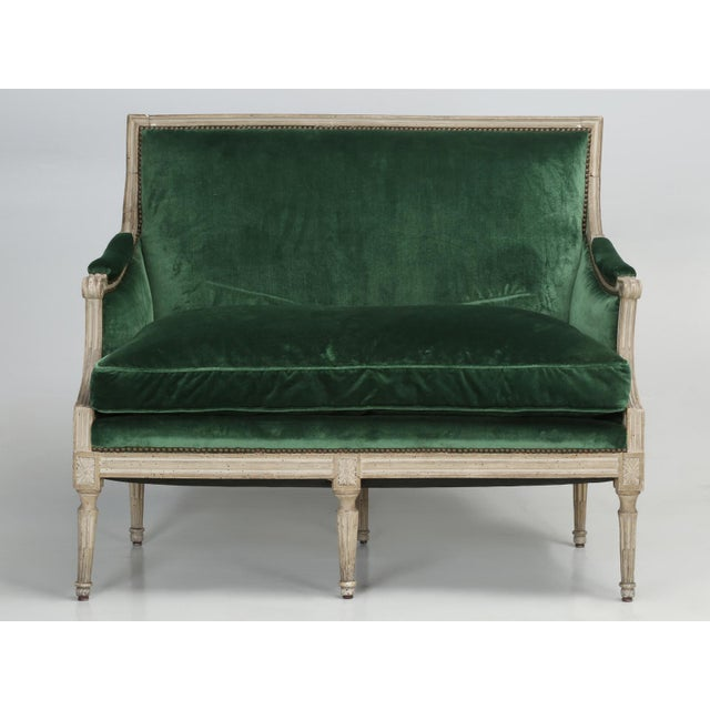 Antique French Louis XVI style settee, with a completely original putty grey painted finish, that has not been enhanced or...