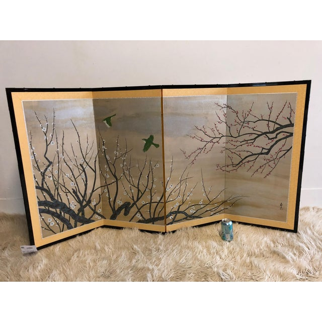 A painted, 4-panel silk screen, depicting flowering cherry blossoms and birds. Signed and stamped, lower right. Very good...