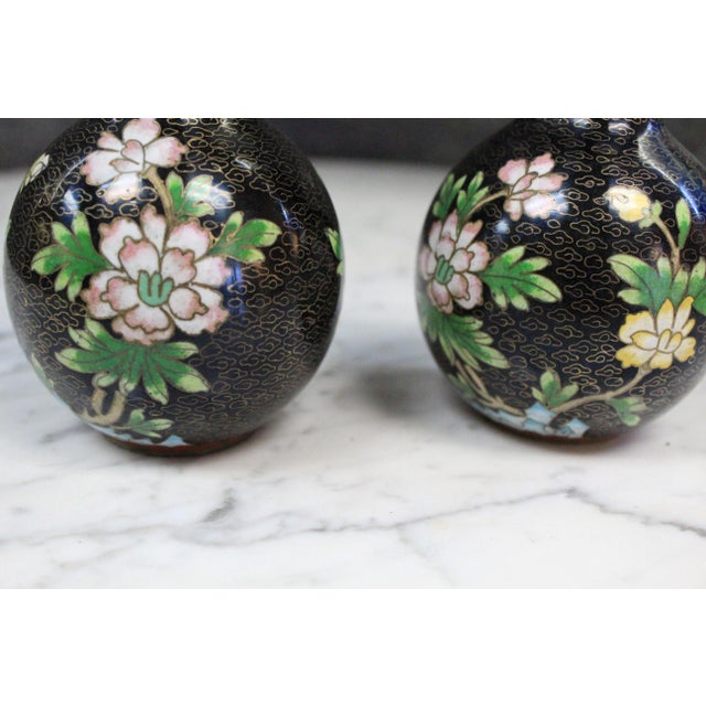 Pair of Asian double gourd form Cloisionee sake bottles with black background and overall multicolor floral decoration....