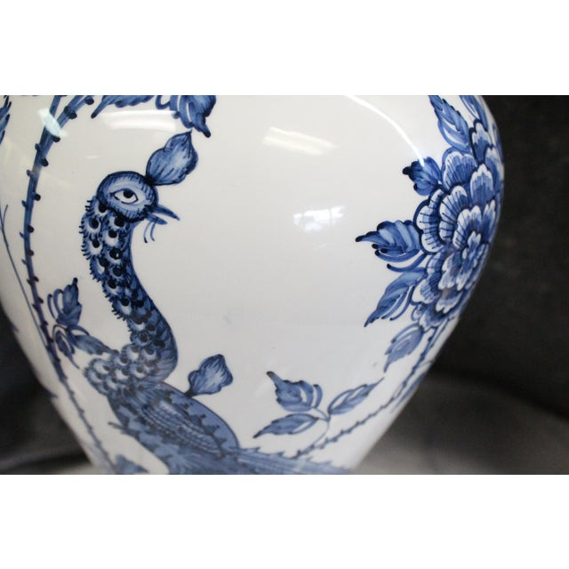 Unique Chinese porcelain lamp in white with a blue floral and peacock pattern.