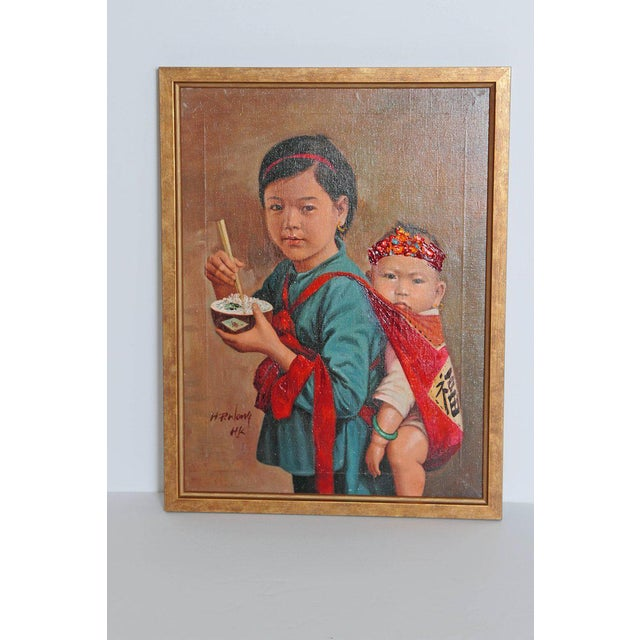 A realistically poised framed oil on canvas of Chinese girl eating rice with her baby sister on her back.