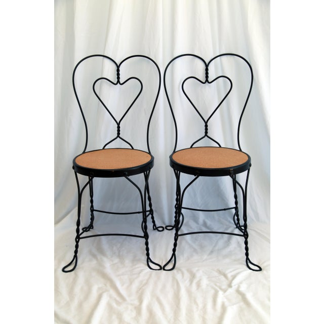 Pair of vintage curly iron ice cream parlor chairs with cork seats. Newly painted in satin black by Fleur de Lex with new...