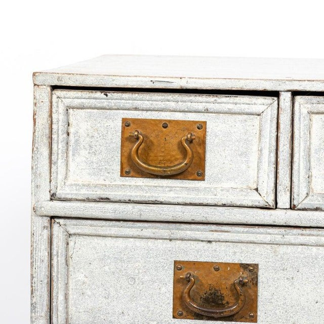 Painted French commode with six drawers and oversized brass hardware, circa 1890s. The piece also features bun turned...