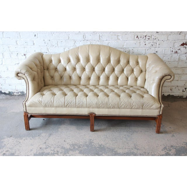 Offering an exceptional vintage tufted tan leather Chesterfield style sofa. The sofa features beautifully aged and...