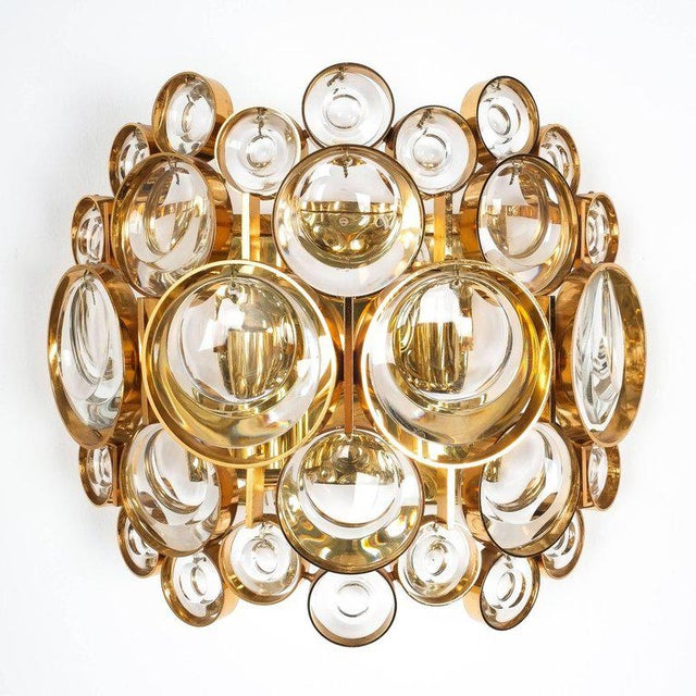 Beautiful pair of large gold-plated brass and smooth optical crystal glass wall lights by Palwa from the 1960s. They are...