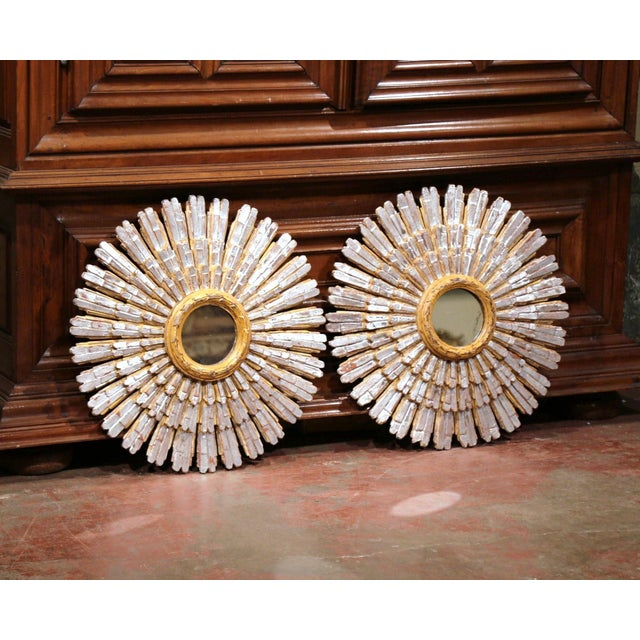 This large pair of vintage sunburst mirrors were carved and painted in France, circa 1940. Each ornate wall hanging mirror...