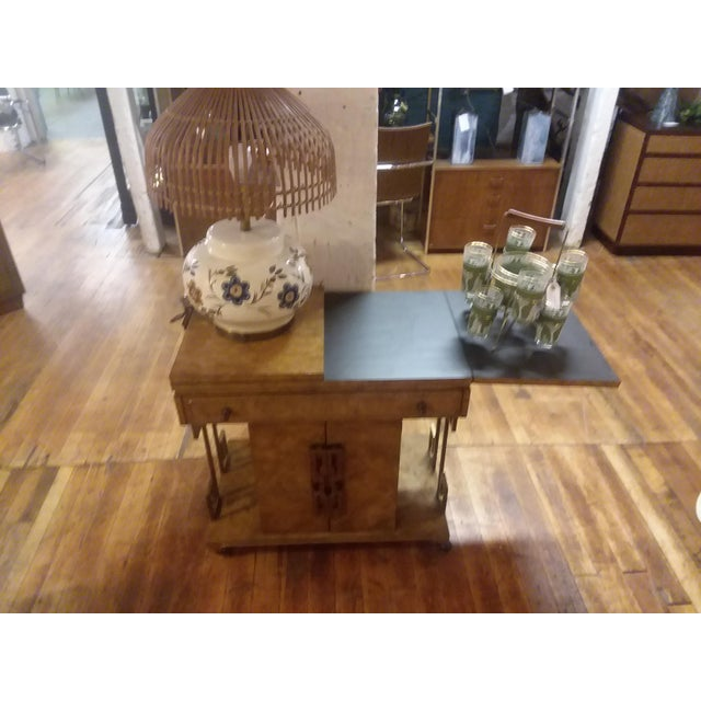 Amazing bar cart from Master Craft. Made from burl olive wood and brass accents. Flip open top with black laminent on the...