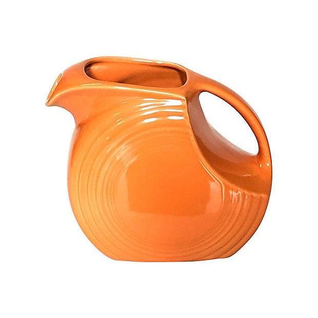 "Classic Fiesta Ware disc pitcher in tangerine. Marked ""Fiesta, USA"" on bottom. Light age."