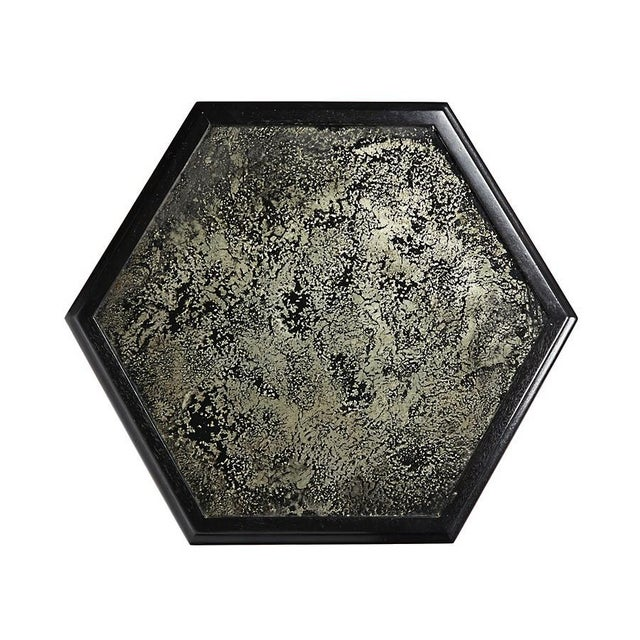 This unique side table is crafted of hand-finished solid wood with an antiqued hexagonal mirrored top. Hand applied stain...