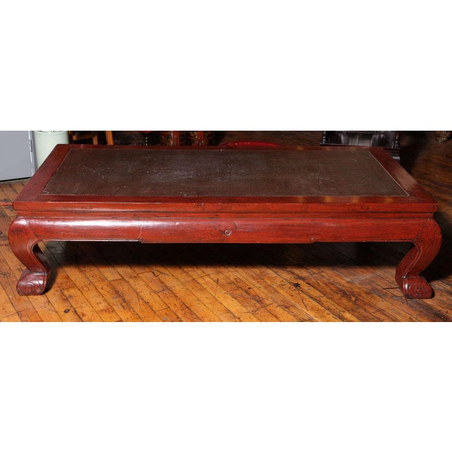 This Chinese 19th century large opium bed coffee table features a rattan insert. The large wood legs are covered with a...