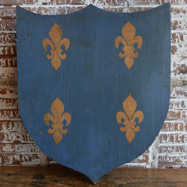 Vintage mid 20th century French painted wood family shield, painted a rich blue with gold fleur de lis pattern. New wire...