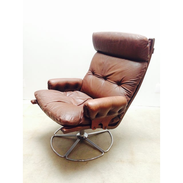 Leather and chrome swivel base brown leather lounge chair. A Westnofa-style bentwood frame features with a chrome flower...