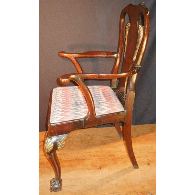 This pair of antique arm chairs in the George II style, in mahogany and mahogany veneer, have superior hand-carved and...