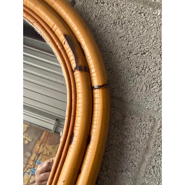 Beautiful vintage bamboo mirror. Oval shape with beautiful patina. Wired for hanging. Acquired from a Palm Beach estate.