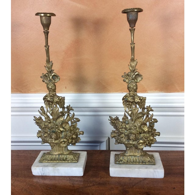 A pair of antique, bronze candle holders with flower basket design and marble base from the 19th century. The lovely...