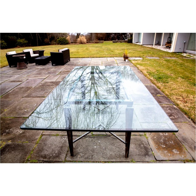 A long, thick glass top rectangular dining table with a beveled-edge, rounded corners and a weathered steel base. The base...