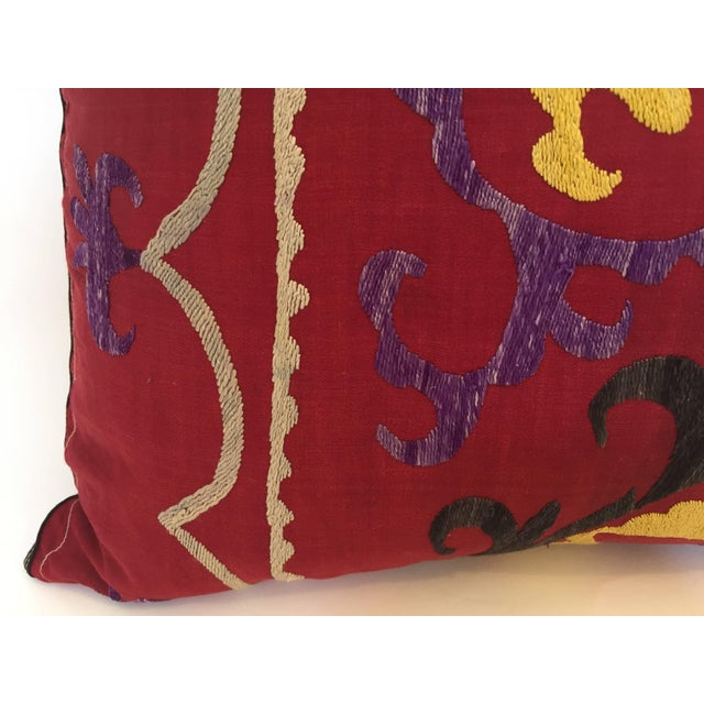 Large vintage colorful Suzani embroidery throw pillow red with colorful threads. A reddish embroidered pillow with flower...
