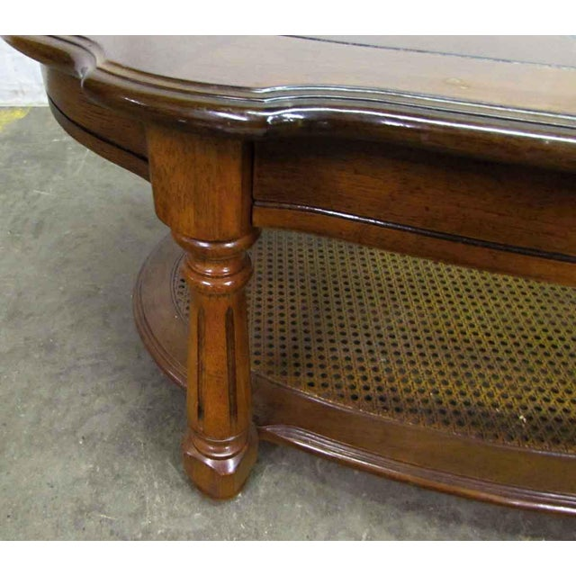 This is an oak oval shaped coffee table with a cut out glass center and four post legs. The second shelving level is a...