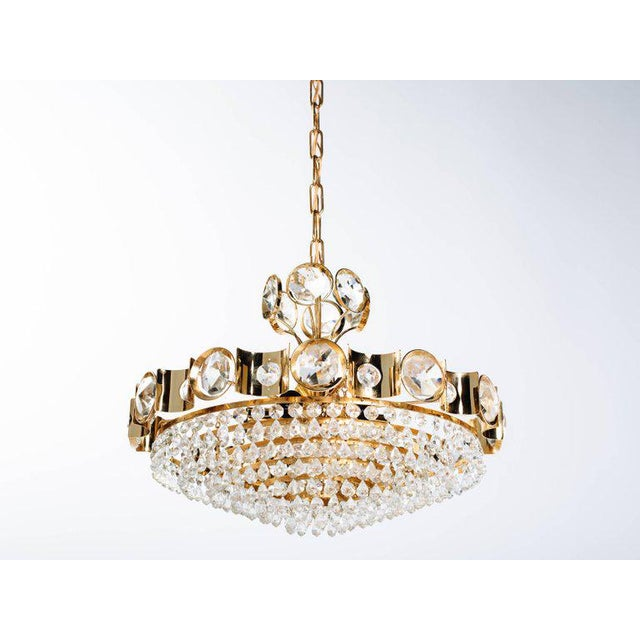 Exquisite Hollywood Regency chandelier with gold-plated over brass frame. The chandelier has a circular multi-tiered...