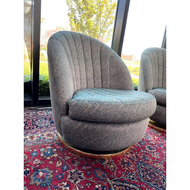 A stunning pair of swiveling club chairs by Milo Baughman for Thayer Coggin featuring elegant channel tufted upholstery...