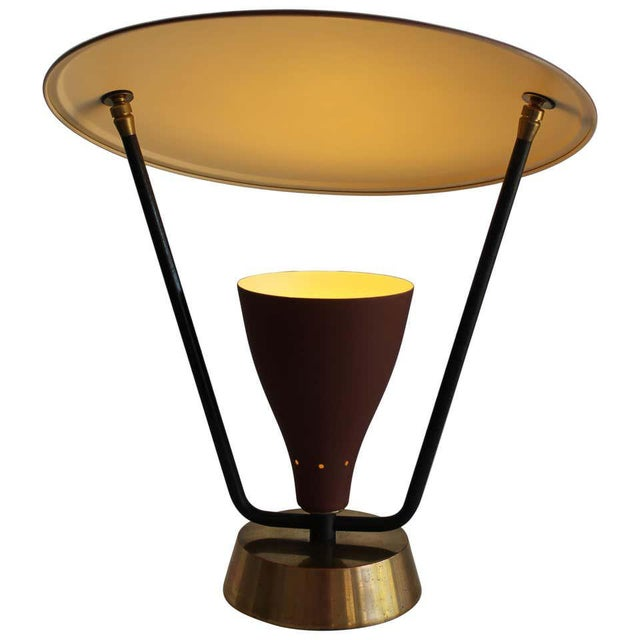 An early 1950s modern lamp with an adjustable saucer light deflector. The light cone is perforated at the base and...