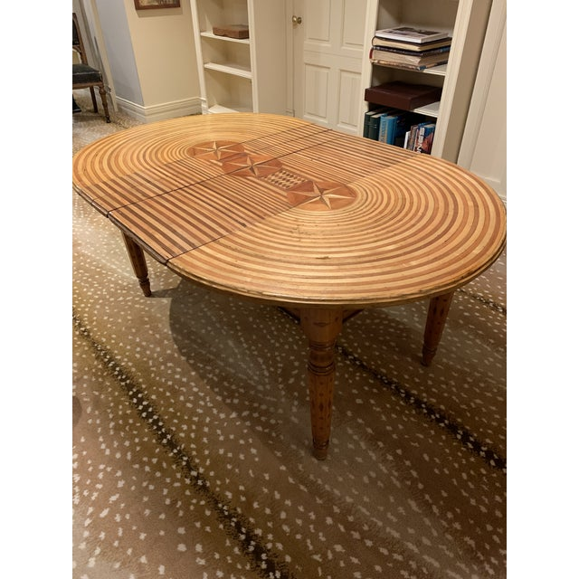An American folk art extendable dining table with fine marquetry top and legs. Unique star and stripe motif top. This...