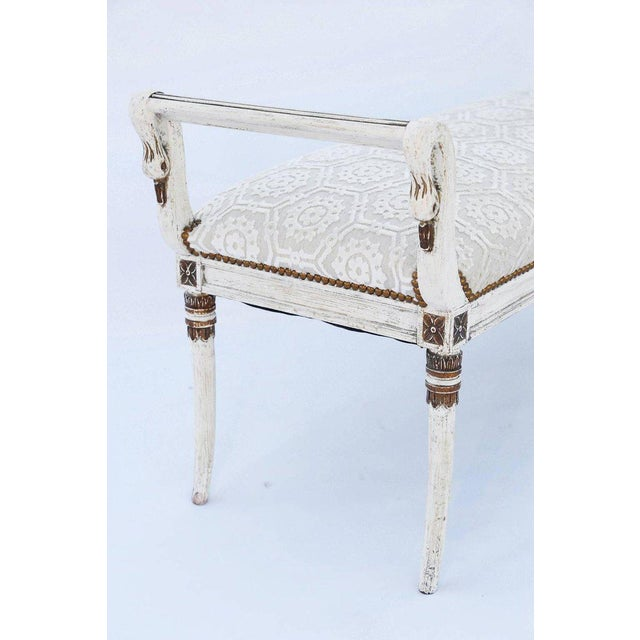 Long bench, painted and parcel-gilt finish showing natural wear, having a crown seat with nailheads, flanked by swan-neck...