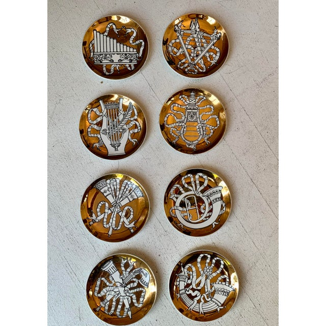 P. Fornasetti MUSICALIA. Plates Set of 8: white wind and string musical instruments on brass back. Signed on the bottom:...