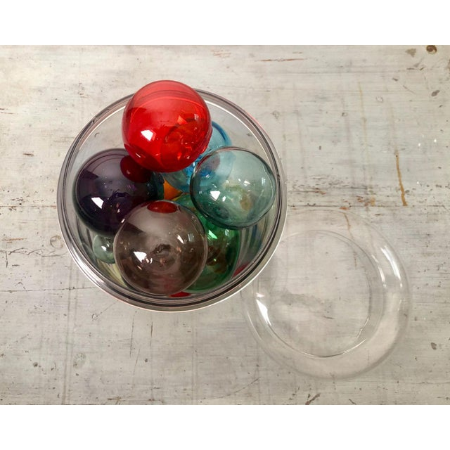 A collection of 21 Vintage colored glass globes in various sizes and colors in an antique glass pharmacy jar. Globes are...