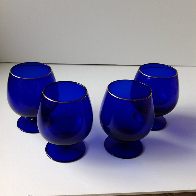 Offered is a set of 4 cobalt blue brandy snifter glasses made by Ralph Lauren featuring bright deep cobalt blue with gold...