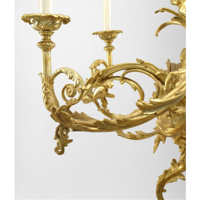 French Louis XV style (19th-20th Century) gilt bronze chandelier with four scroll arms and two cupid mermaid figures on a...