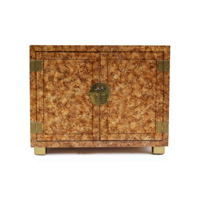 Henredon cabinet in a faux tortoise finish with brass hinges and closure and brass capped legs. The maker employed an oil...