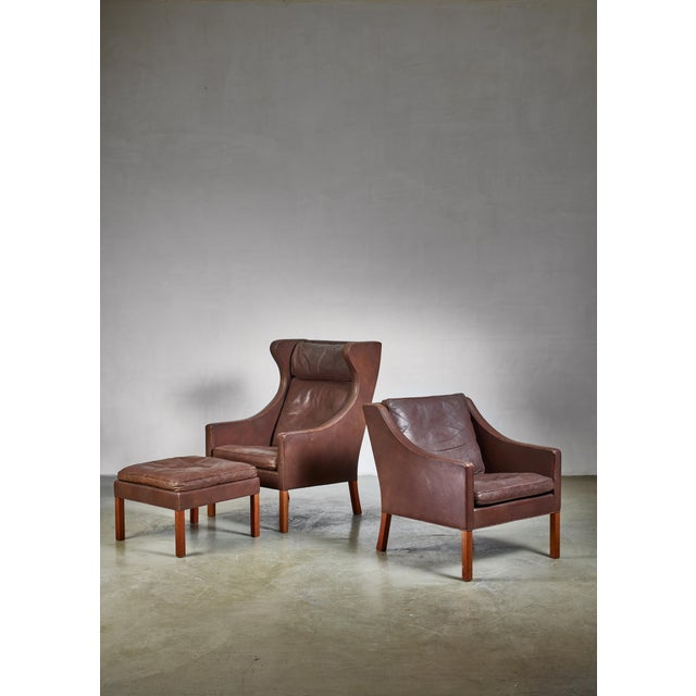 A Børge Mogensen for Fredericia set of two lounge chairs plus ottoman in dark brown leather. The measurements stated are...