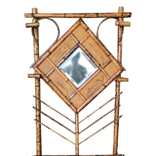 Antique tiger bamboo hall tree with handwoven rice mat and decorative square/diamond center piece. The hall tree features...