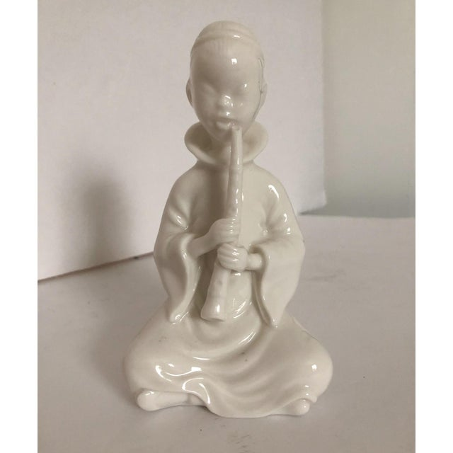 Remarkably detailed porcelain Blanc de Chine flute player with an intricate braid. Unmarked.