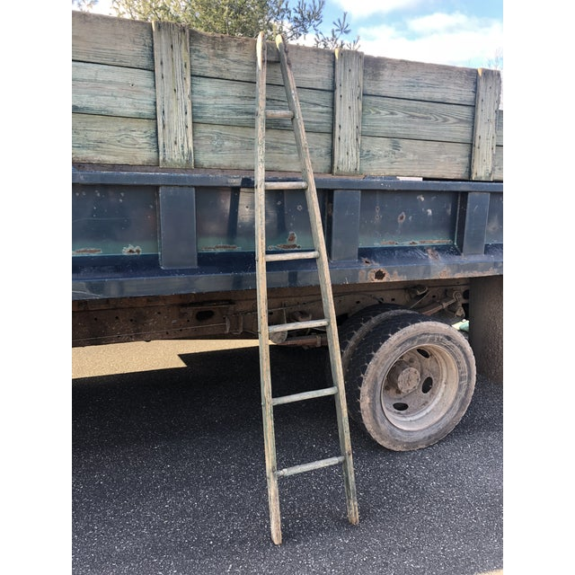 A wonderful tall antique apple ladder from Maine having original vestiges of faded green paint on distressed wood.